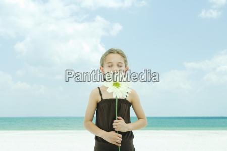 girl holding up flower eyes closed