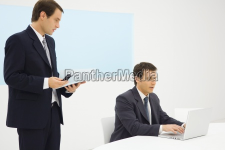 two businessmen in office looking down