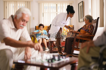 hospice doctor measuring blood pressure to