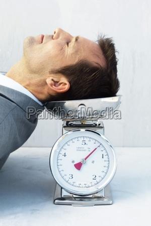 man resting head on scale eyes