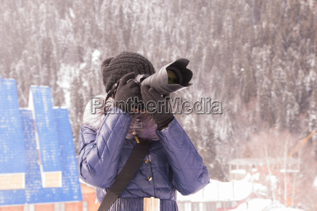 a young girl takes pictures winter