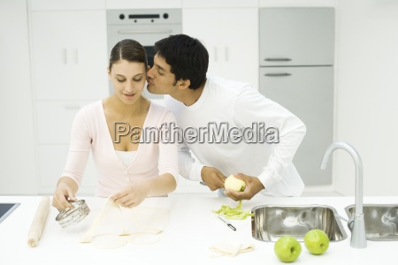 couple cooking together man kissing womans