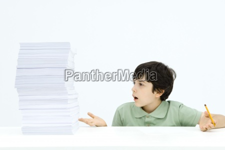 boy looking at tall stack of