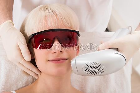 woman receiving laser epilation treatment at