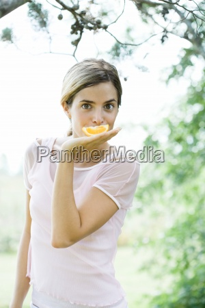 young woman holding orange slice in