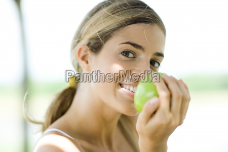 woman holding up apple glancing at