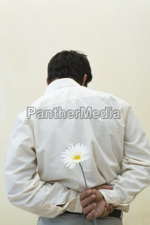 man holding flower behind his back