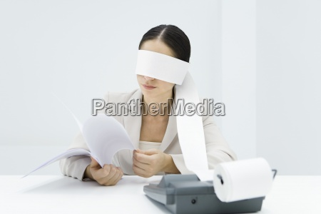 female accountant blindfolded with paper from