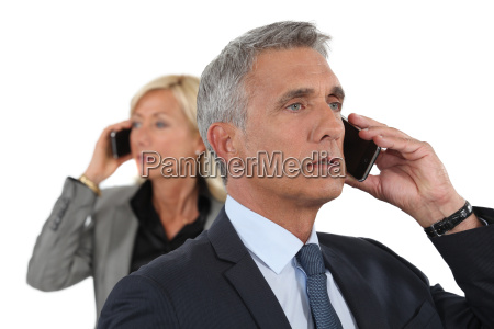mature business couple using cellphones