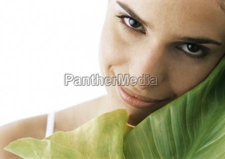 woman tilting head against green leaf