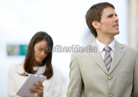 businessman looking up while female assistant