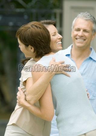 two mature women hugging while man