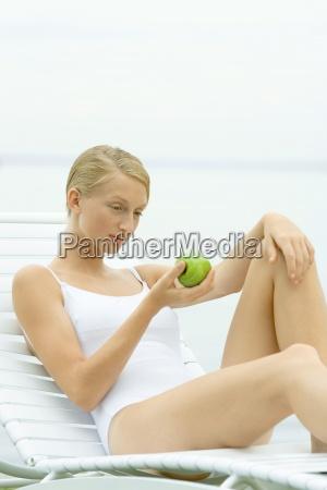 teenage girl in swimsuit sitting on