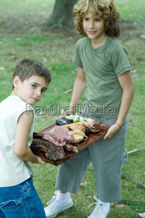 two boys carrying tray of grilled
