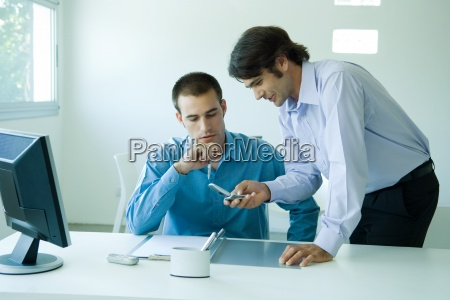 two young businessmen in office using