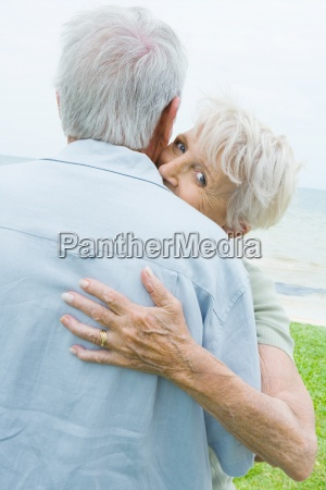 senior couple hugging woman looking over