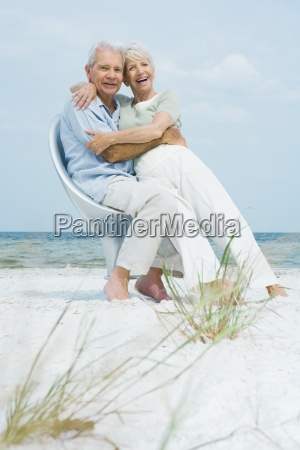 senior couple sitting in chair together