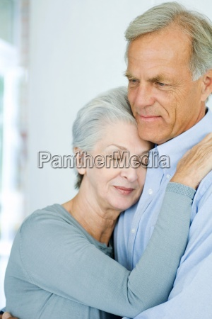 mature couple embracing womans eyes closed