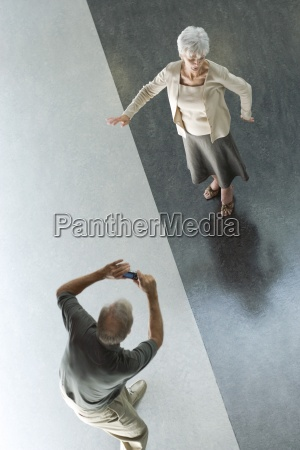 man photographing wife with digital camera