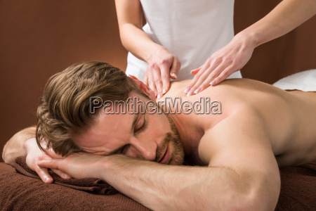 young man receiving back massage at