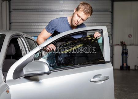 applying tinting foil onto a car