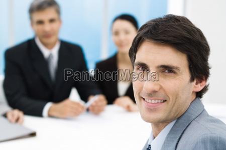 businessman in meeting smiling at camera