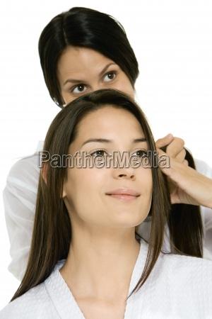 hair stylist fixing womans hair