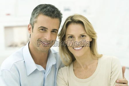 couple smiling at camera mans arm