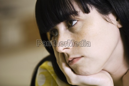 young woman contemplatively looking away