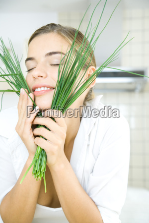 young woman holding chives up to