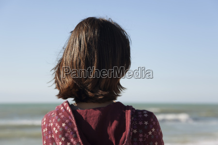 woman contemplating the ocean rear view