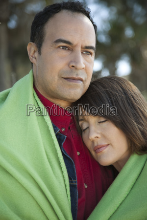 mature couple sharing blanket outdoors portrait