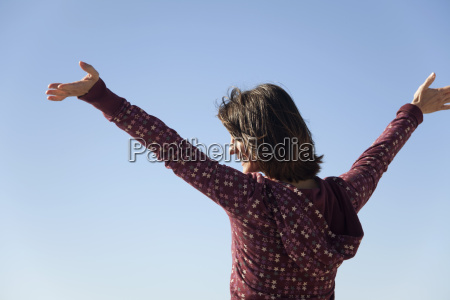 woman outdoors with arms raised in