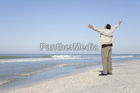 man standing on beach looking at
