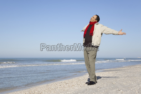 man standing on beach with arms