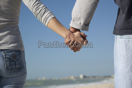 couple holding hands outdoors cropped