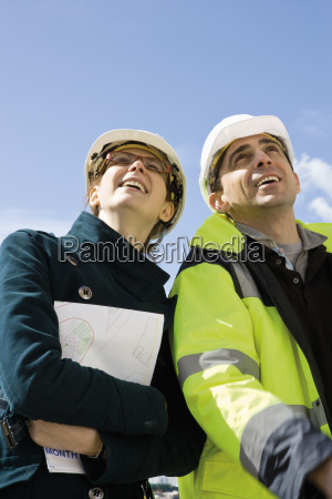 business woman and building contractor smiling
