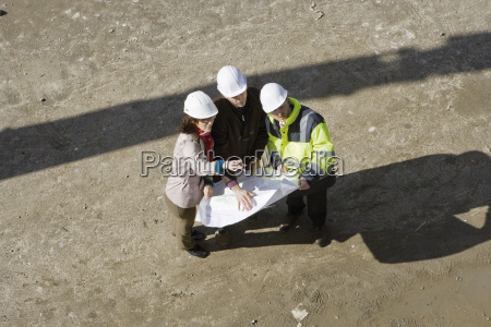 contractor and business people discussing blueprint
