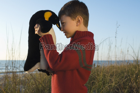 boy nuzzling stuffed toy penguin