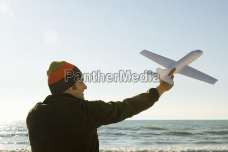 young man at beach holding aloft