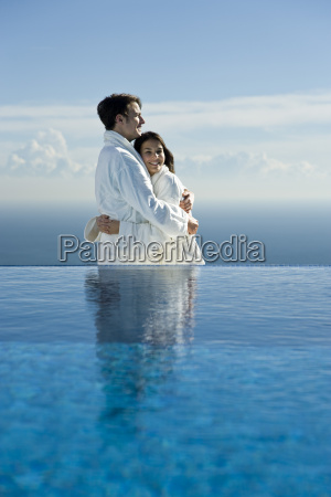 couple embracing at edge of infinity