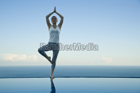 woman standing in tree pose on