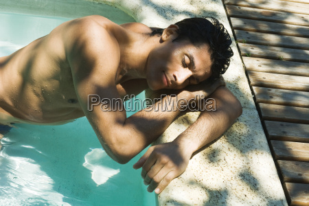 man leaning against side of swimming