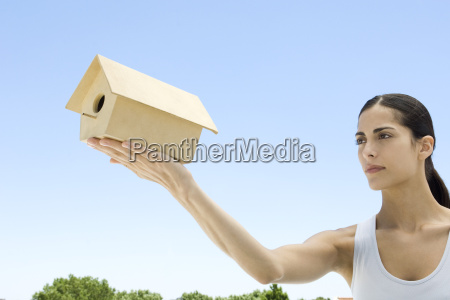 woman holding up birdhouse