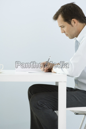 man sitting at table writing side