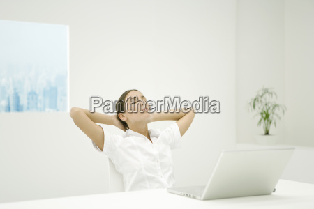 woman leaning back at desk hands