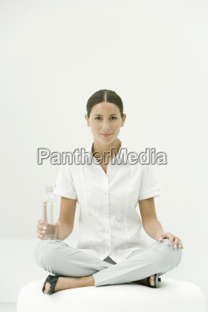 woman sitting cross legged holding water