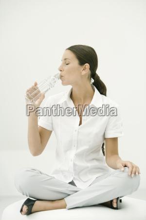 woman sitting cross legged drinking water