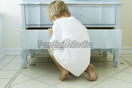 boy crouching snooping in chest of
