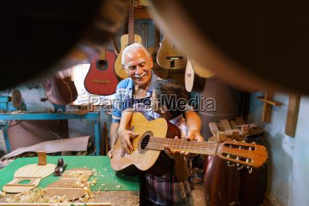 boy learns play guitar with senior
